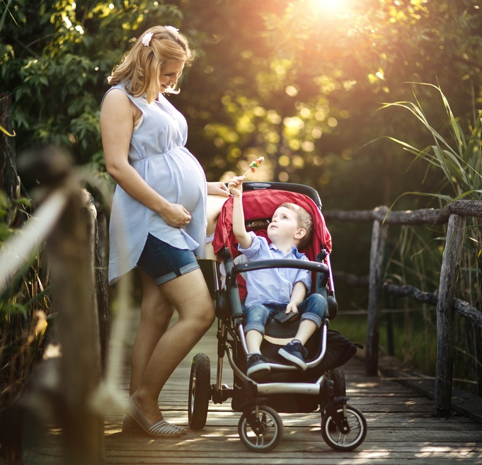 pregnant woman with child in pushchair