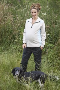posing in a maternity fleece with her dog in the countryside